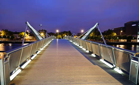 eventide: Illuminated pedestrian bridge across river Liffey in Dublin photographed in twilight