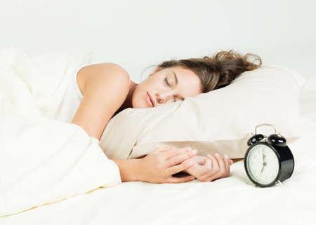 woman clock: Bastante joven duerme en su cama