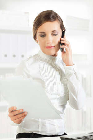 Pretty young businesswoman reading papers while speaking on the phone photo