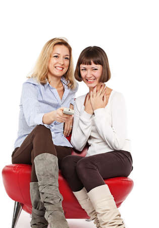 woman watching tv: Two amused young woman watching TV; isolated on white Stock Photo