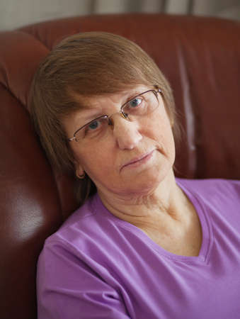 neutral face: Elder woman sitting in a leather armchair at home; wearing glasses; having neutral face expression Stock Photo