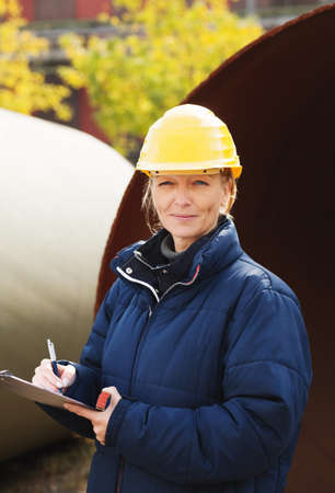 Female engineer in yellow hard hat taking notes at construction site