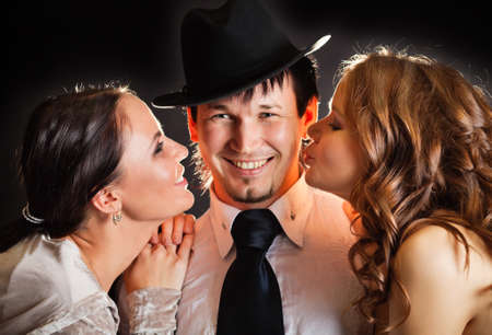 two pretty young women kissing smiling man from the sides photo