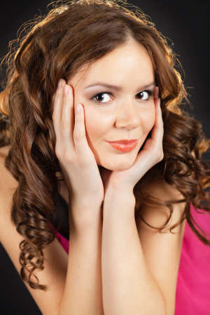 Portrait of a pretty young woman holding her face in her palms Stock Photo