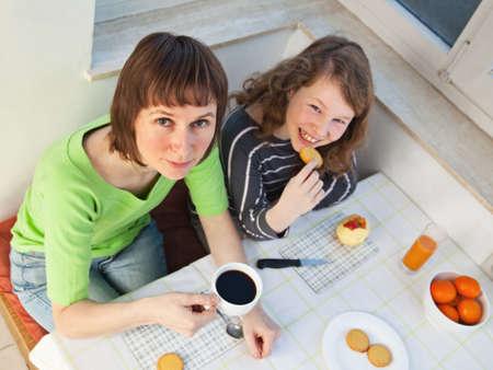 ハイアングルビュー: 娘と彼女のお母さんが一緒に、朝食を持っています。高角度のビュー。
