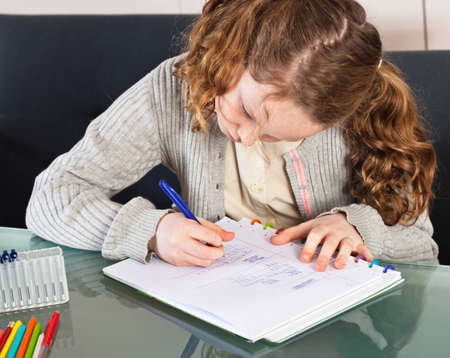 Teenager girl sitting at the table at home and doing her homework photo