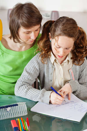 Teenager girl sitting together with her mother and showing her homework Stock Photo