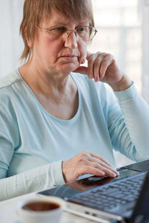 Elder woman working with laptop computer at home photo
