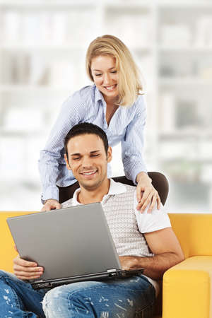 Happy young man and woman sitting together and looking at computer screen photo