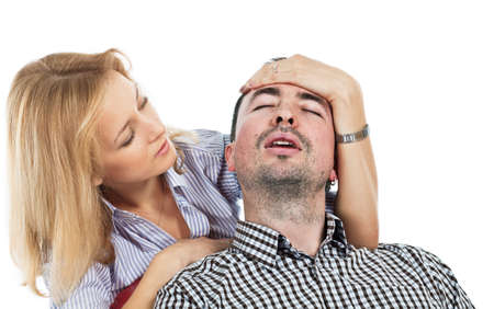 cephalgia: Anxious pretty young blond woman holding her hand on the forehead of his boyfriend suffering from headache Stock Photo