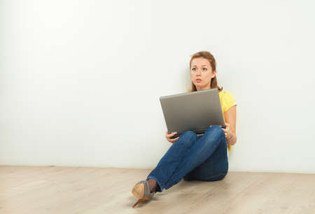 Pretty young blond woman sitting on the floor with laptop computer Stock Photo