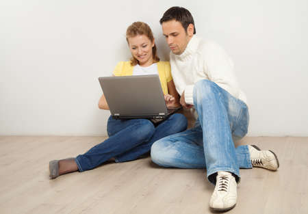 Happy young couple sitting on the floor with laptop computer photo