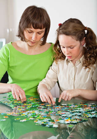 Teenager girl and her mother doing a puzzle at home photo