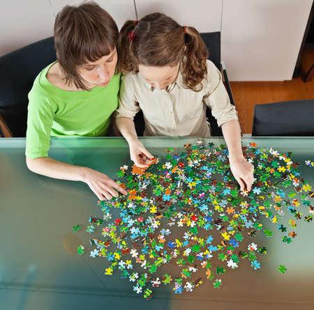 Dospívající dívka a její matka dělá puzzle doma