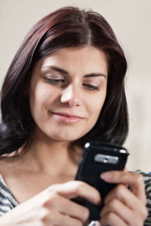 Pretty smiling brunette woman texting with her cellphone
