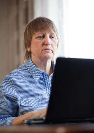 Elderly woman working with laptop computer at home photo