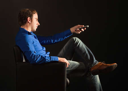 Handsome man sitting on the armchair in the dark changing TV channeels with remote control Stock Photo