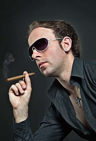 Young cool guy in sunglasses smokes cigar Stock Photo