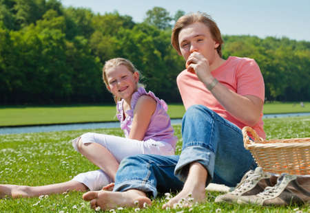 Teenager brother and sister having a picnic in the park in a bright sunny day photo