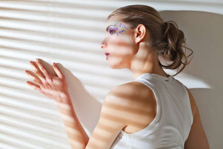 Pretty young woman lean lit by bright sunlight coming through the blinds photo