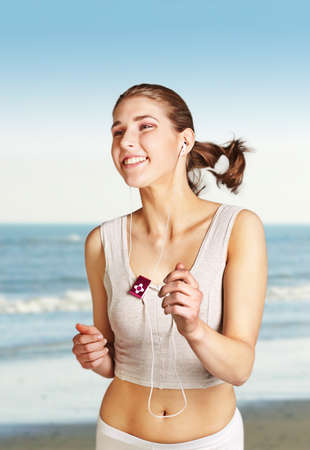 Pretty young woman jogging on the beach Stock Photo