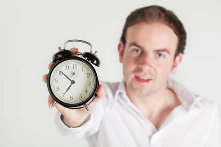 Man holding alarm clock towards the camera. Clock dial in focus, man out of focus. photo
