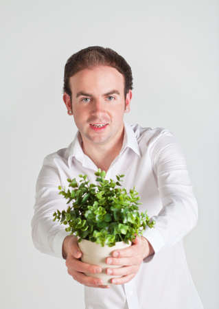Happy young man holds a pot with decoration plant photo