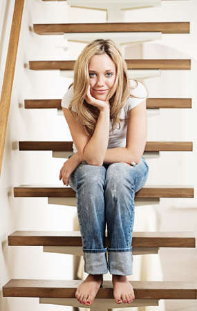 Pretty young smiling woman sitting on steps at home Stock Photo - 9714869