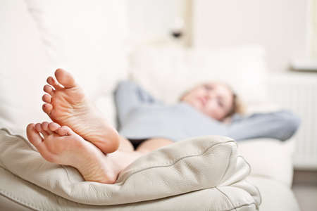 resting: Barefoot young woman lying on sofa, shallow depth of field, focus on foot soles Stock Photo