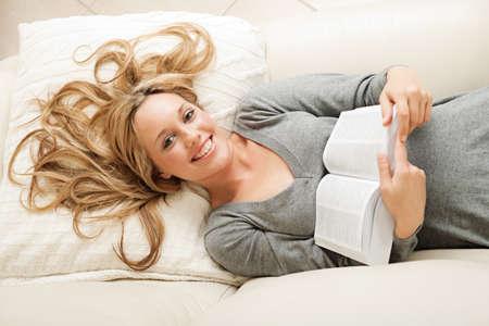 ハイアングルビュー: ハイアングル笑みを浮かべて本をソファーに横になっている金髪の女性