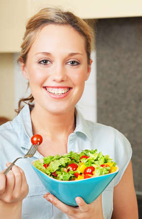 Pretty smiling young woman standing in the kitchen and holding a bowl with salad Stock Photo
