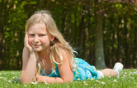 Blond teenager girl lying on the grass in a bright sunny day Stock Photo