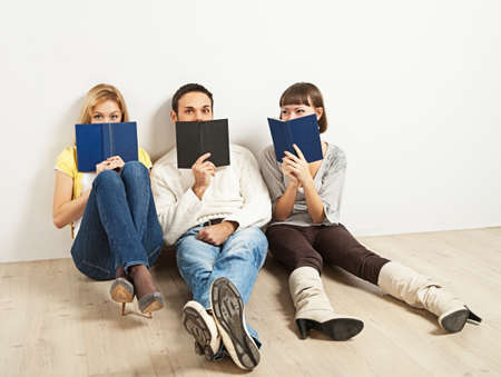 Three kidding students with books - one man and two women photo