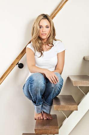 mujeres sentadas: Bastante joven sonriente sentado en los escalones en su casa