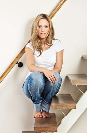 Pretty young smiling woman sitting on steps at home Stock Photo - 10821539