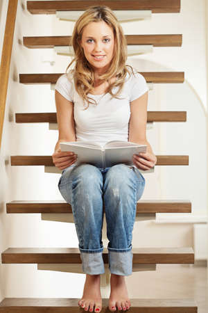 Pretty young smiling woman sitting on steps at home Stock Photo - 10821534