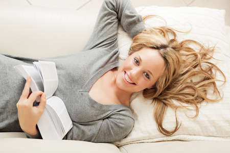 resting: High angle view on smiling blond woman lying on sofa with book