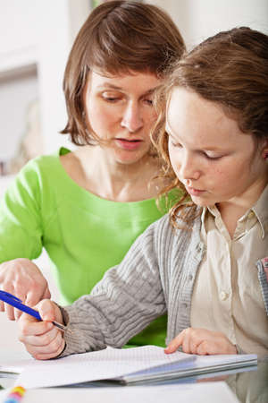 homework student: Mother helping her teenager daughter to do a homework