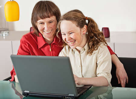 kids laptop: Mother and teenager girl with laptop computer together at home Stock Photo
