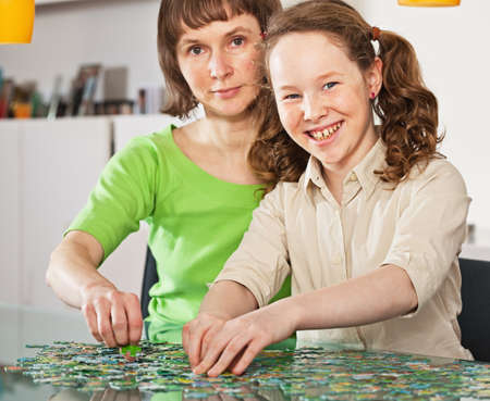 Teenager girl and her mother doing a puzzle at home Stock Photo - 10821631