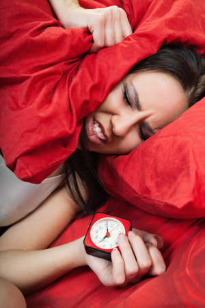 irritated young woman lying in bed and closing her ears with pillow  Stock Photo