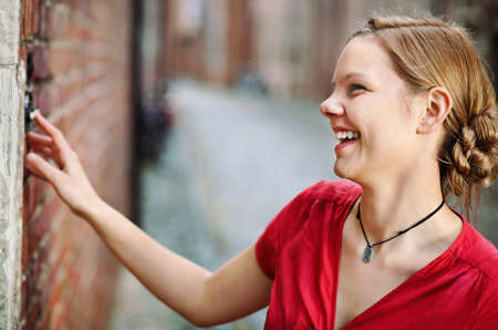 door bell: Pretty young smiling woman ringing at the door bell  Stock Photo