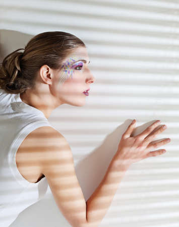 Pretty young woman lean lit by bright sunlight coming through the blinds Stock Photo - 12065491