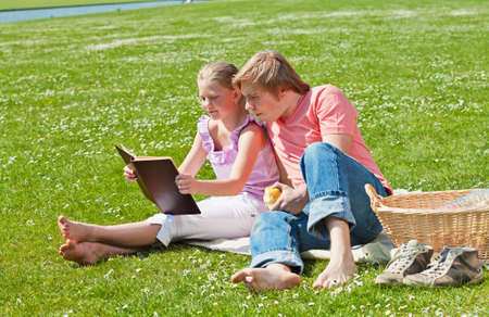 Teenager siblings reading book at picnic in the park in a bright sunny day Stock Photo