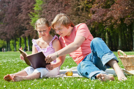 Teenager siblings reading book at picnic in the park in a bright sunny day photo