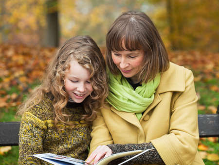 Mother and her teenager daughter sitting with a book on a bench in an autumn park Stock Photo - 15174229