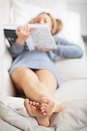 Barefoot mladá žena ležela na pohovce a čtení knihy Reklamní fotografie
