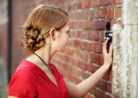 campanas: Anillos rubia bastante joven mujer en el timbre de la puerta Foto de archivo