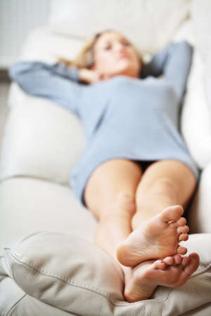Barefoot young woman lying on sofa, shallow depth of field, focus on foot soles photo