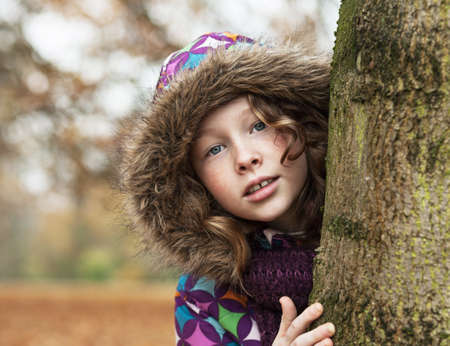 poking: Teenager girl in colorful jacket poking around a tree trunk in an autumn park Stock Photo